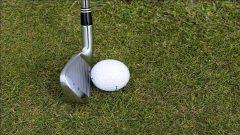 A golf ball next to a golf club